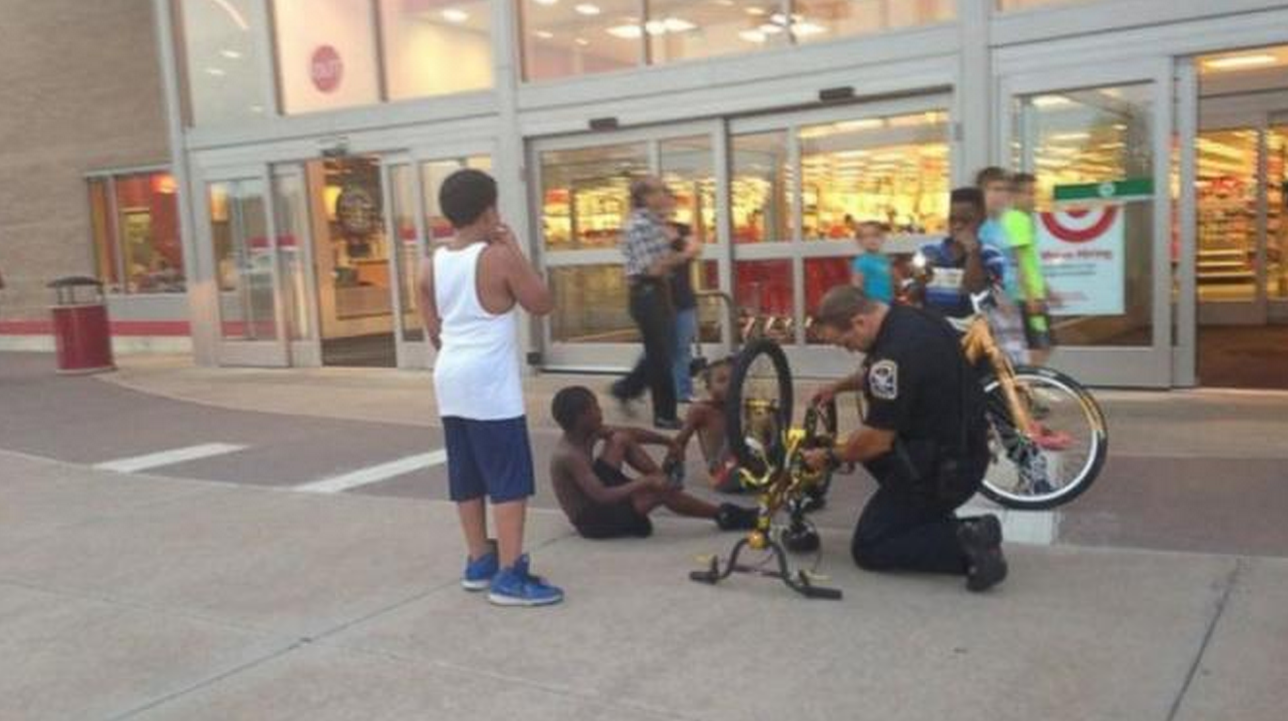 Photo of police officer fixing kid's bike goes viral